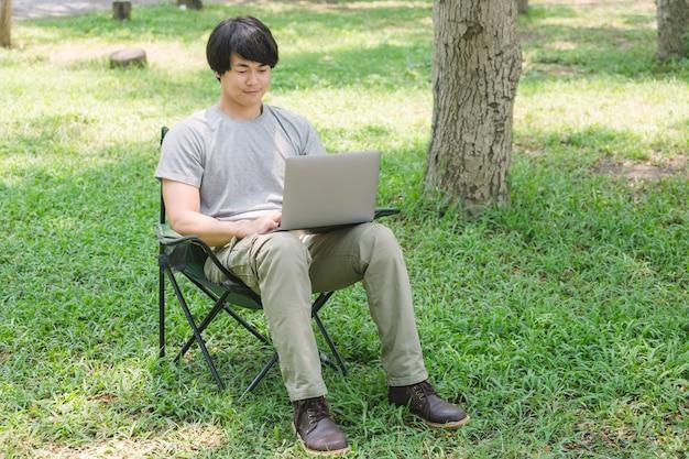 Hombre sentado en una silla de camping y trabajando con una computadora portátil en el jardín