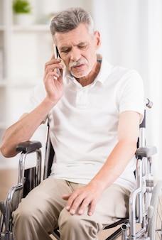 Hombre sentado en silla de ruedas en casa y hablando por teléfono.