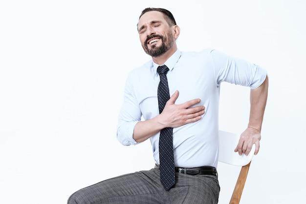 Un hombre sentado en una silla se siente mal, tiene un mal corazón.