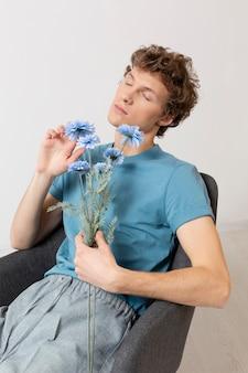 Hombre sentado en una silla y sosteniendo flores