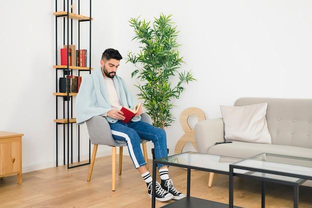 Hombre sentado en una silla con una toalla sobre su hombro leyendo el libro en casa