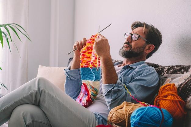 Hombre sentado en el sofá aprendiendo a tejer con lana coolorful. trabajo de tejer actividad de ocio interior hombres relajándose en el sofá. concepto de tiempo de hobby