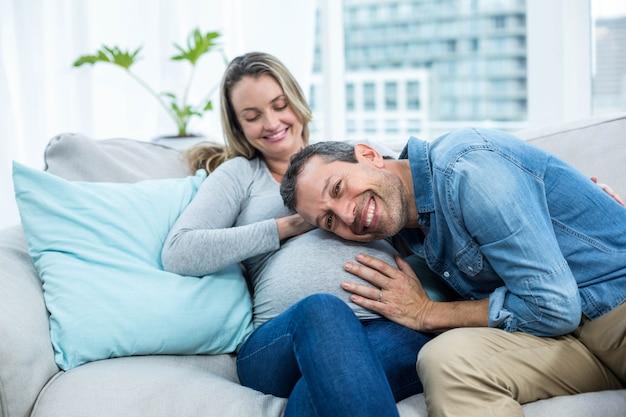 Hombre sentado en el sofá y escuchando el estómago de la mujer embarazada