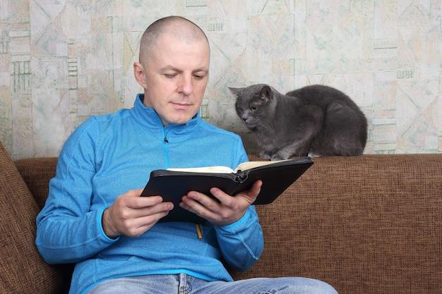 Hombre sentado en el sofá y leyendo un libro de la biblia