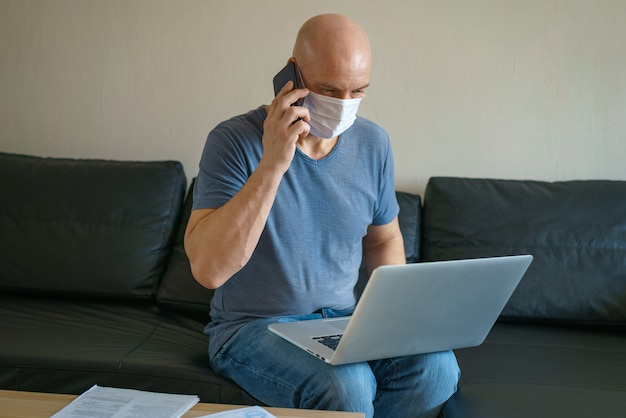 El hombre está sentado en un sofá con una máscara protectora con una computadora portátil y un teléfono, trabajo remoto en cuarentena