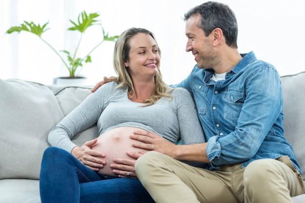 Hombre sentado en el sofá y sosteniendo el estómago de la mujer embarazada