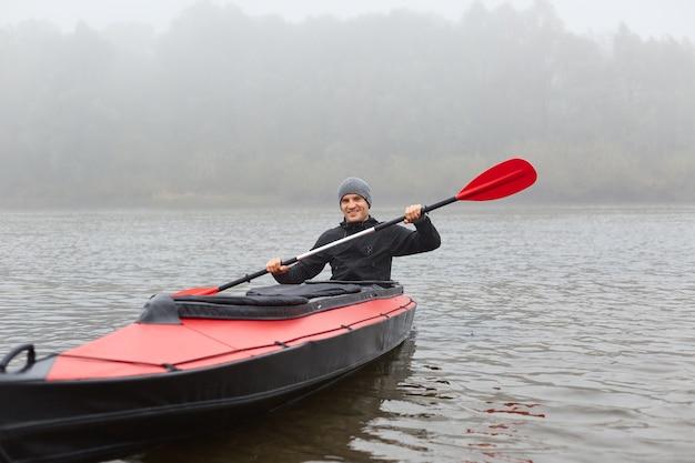 Hombre sentado sonriendo en kayak y sosteniendo la paleta en las manos