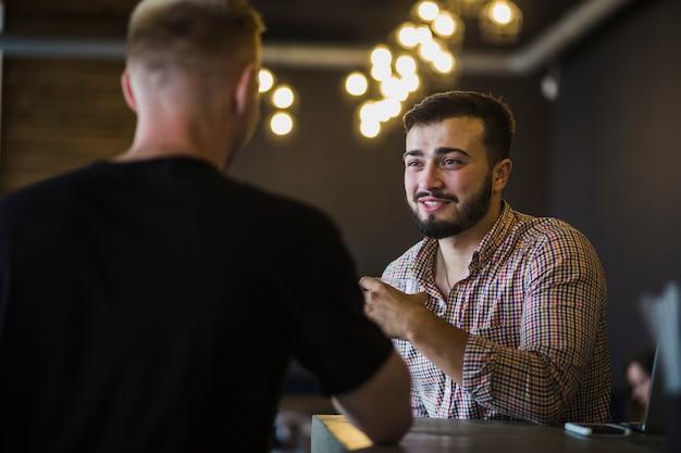 Hombre sentado con su amigo disfrutando de bebidas en el restaurante