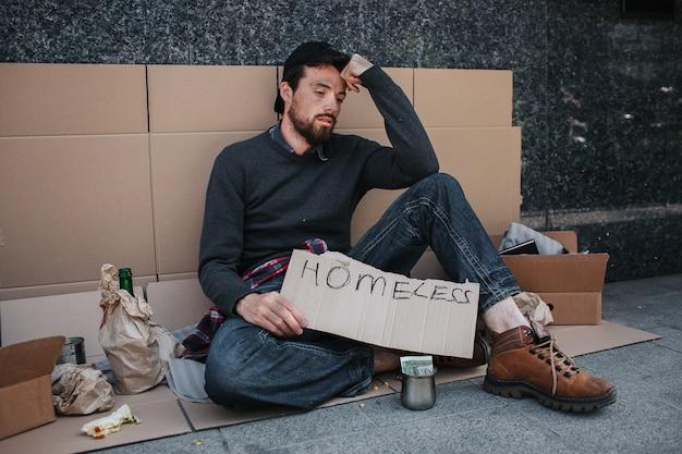 Hombre sentado en el suelo y con cartón sin hogar en sus manos