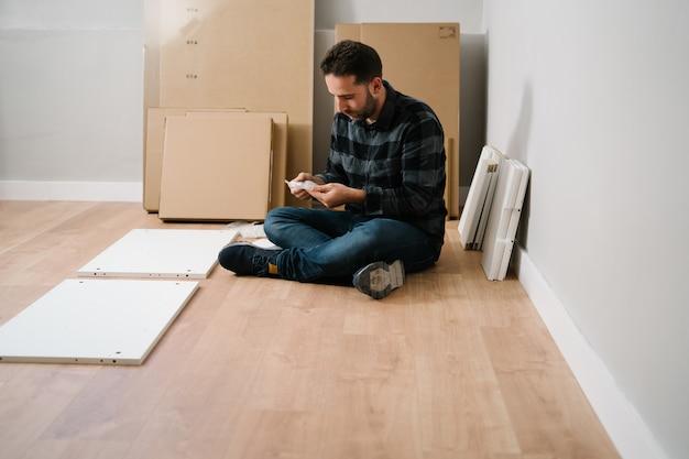 Hombre sentado en el suelo montando muebles. hágalo usted mismo montaje de muebles.