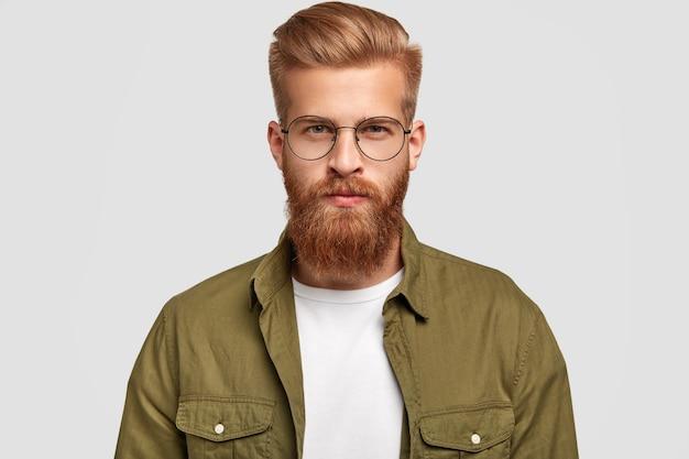 Hombre serio sin afeitar con cabello y barba pelirrojos, mira directamente, piensa en algo, viste camisa de moda y gafas redondas, aisladas sobre una pared blanca. concepto de masculinidad