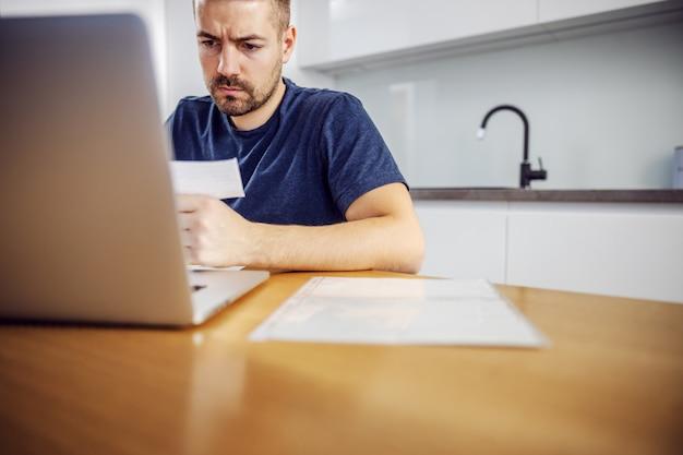 Hombre serio barbudo con el ceño fruncido joven sentado en la mesa de comedor, sosteniendo la factura y usando la computadora portátil para pagarla.