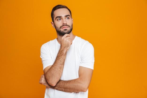 Hombre serio en camiseta tocando su barbilla mientras está de pie, aislado en amarillo