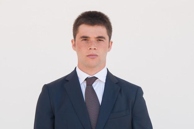 Hombre serio en chaqueta formal y corbata de pie para cámara