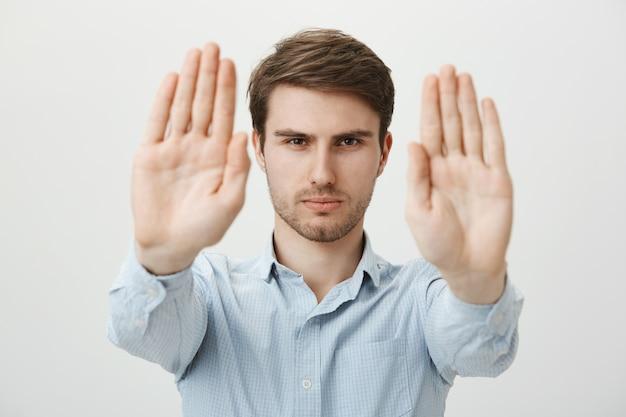 Hombre serio confiado extiende las manos a la parada de la tienda, advertencia o restricción