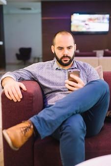 Hombre serio con estilo con teléfono en casa