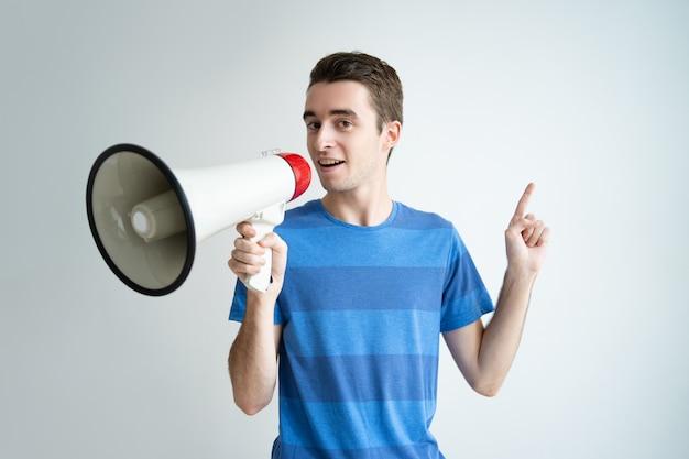 Hombre serio hablando en megáfono y apuntando hacia arriba.
