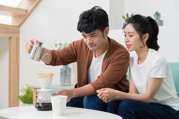 Hombre serio con hervidor de cuello de cisne y filtro de papel grueso para preparar café en casa, y la mujer lo acompaña.