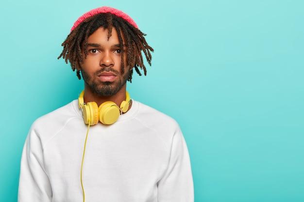 Hombre serio hipster con rastas, viste sombrero rosa y suéter blanco, tiene auriculares para escuchar pistas de audio, pasa tiempo libre siempre escuchando música