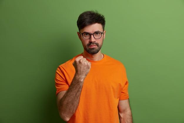Hombre serio indignado sacude el puño, promete venganza, dice que te mostraré, advierte sobre algo, mira a través de anteojos, usa camiseta naranja, expresa emociones negativas, aislado en una pared verde