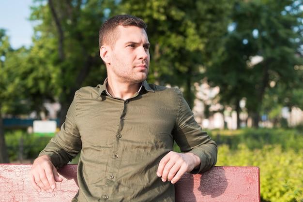 Hombre serio joven que se sienta en banco en parque