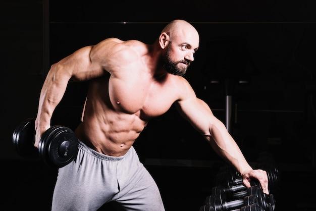 Hombre serio levantando pesas pesadas
