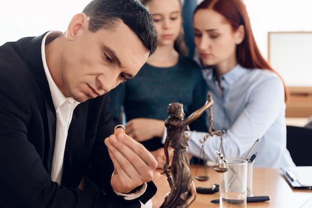 El hombre serio mira el anillo de bodas mientras que se sienta en oficina