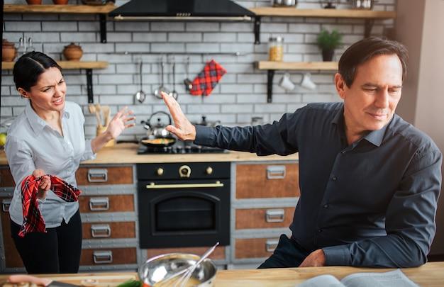 Hombre serio y molesto sentarse a la mesa en la cocina.