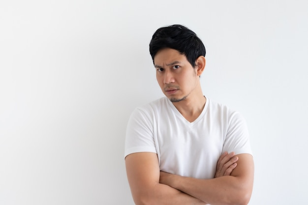 Hombre serio y molesto viste camiseta blanca aislado sobre fondo blanco.