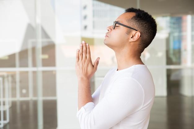 Hombre serio con los ojos cerrados poniendo las manos en posición de oración.