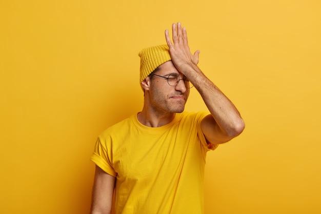 El hombre serio se olvidó de una reunión importante, golpea la palma de la mano en la frente, tiene sentimientos de arrepentimiento, recuerda la tarea, usa ropa informal, modelos contra el espacio amarillo