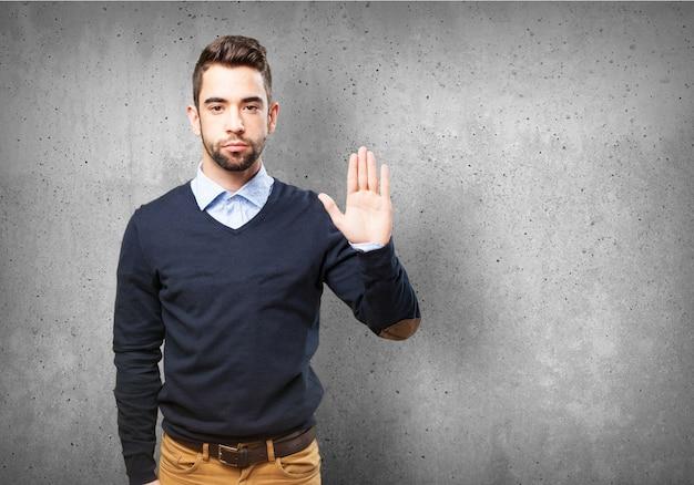 Hombre serio con una palma levantada