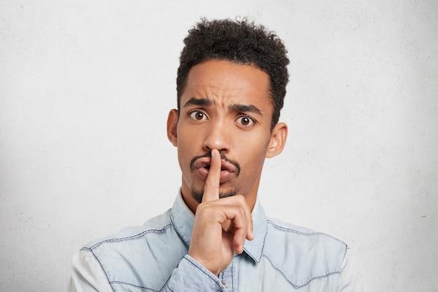 Hombre serio de piel oscura mantiene el dedo en los labios, pide silencio