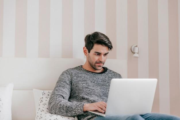 Hombre serio que usa la computadora portátil en cama