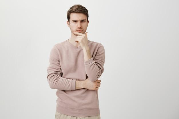 Hombre serio reflexivo entrecerrar los ojos escéptico, pensando como hacer una elección