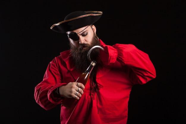 Hombre serio con ropa de pirata para halloween y un parche en los ojos abriendo una botella. hombre guapo disfrazado de bandido.