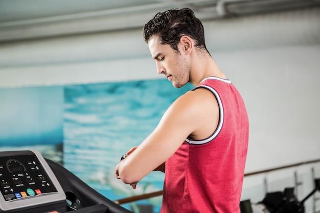 Hombre serio en la rueda de ardilla que mira el reloj elegante en el gimnasio