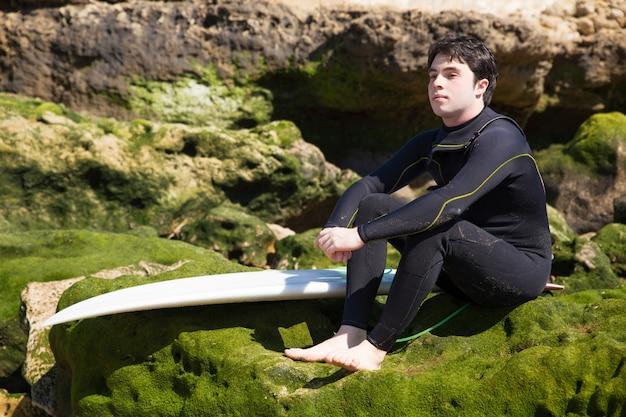 Hombre serio sentado en rocas cubiertas de musgo con tabla de surf