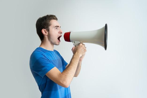 Hombre serio sosteniendo megáfono y gritando en él