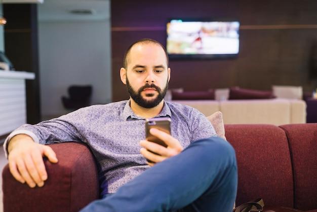 Hombre serio con teléfono en casa