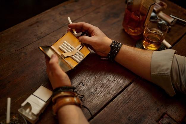 Hombre serio tiene pitillera, estantería y rico interior de oficina. cultura del tabaquismo, sabor específico. hábito de fumar