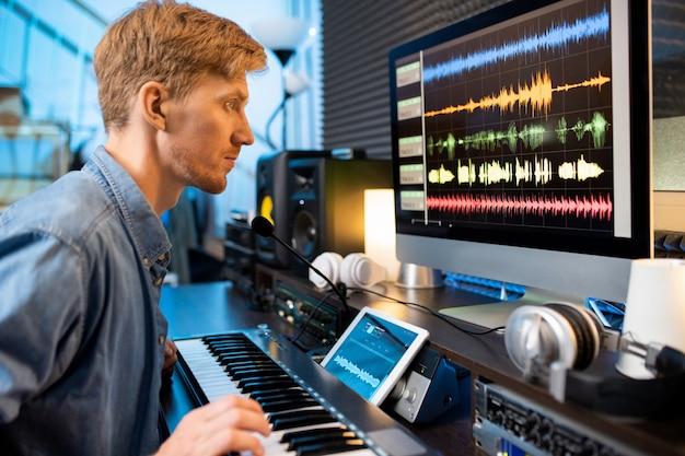 Hombre serio tocando una de las teclas del piano mientras mira formas de onda de sonido en la pantalla de la computadora en frente