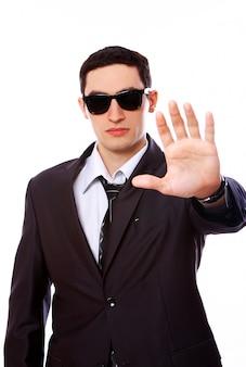 Hombre serio en traje muestra señal de stop