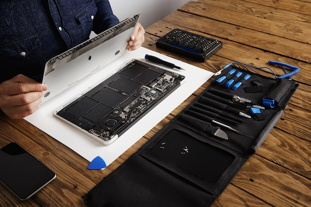 El hombre de servicio abre la tapa de la carcasa trasera de la computadora portátil antes de repararla, limpiarla y arreglarla con sus herramientas profesionales de la caja de herramientas cerca de la mesa de madera