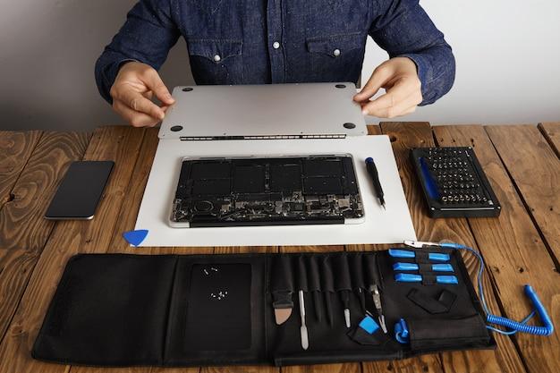 El hombre de servicio abre la tapa de la carcasa trasera de la computadora portátil antes de repararla, limpiarla y arreglarla con sus herramientas profesionales de la caja de herramientas cerca de la vista frontal de la mesa de madera