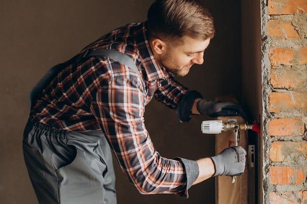 Hombre de servicio ajustando el sistema de calefacción de la casa