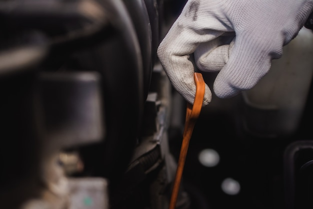 Hombre de servicio comprobando el motor de aceite del coche, cerca de la varilla de control de aceite o varilla medidora de aceite