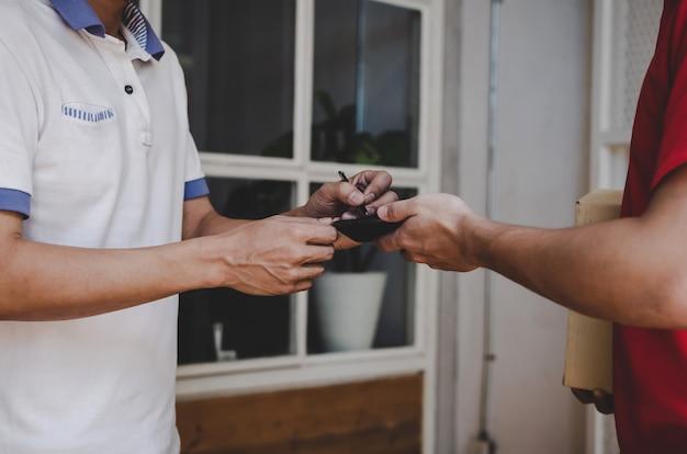 Hombre de servicio de entrega a domicilio en uniforme rojo y cliente joven firma adjunta