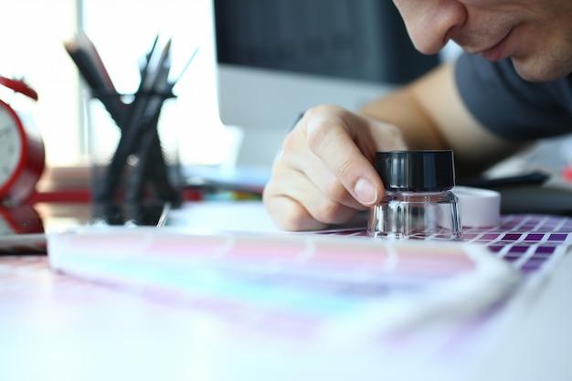 Hombre de servicio masculino sostenga en la mano lupa haciendo prueba de color
