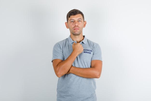 Hombre de servicio técnico de pie con el puño cerrado en camiseta gris y mirando serio